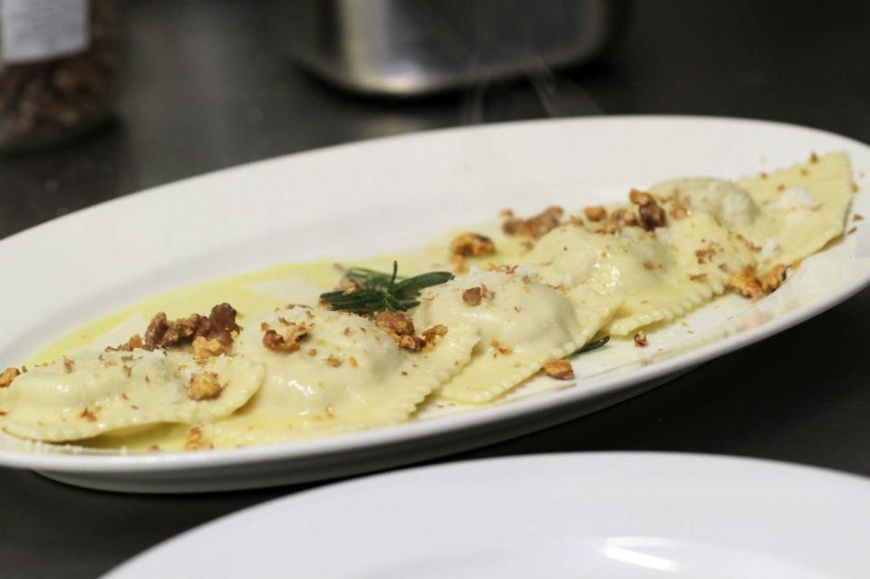 Ravioli fatti in casa ripieni di porri, ricotta e parmigiano in salsa di burro e noci