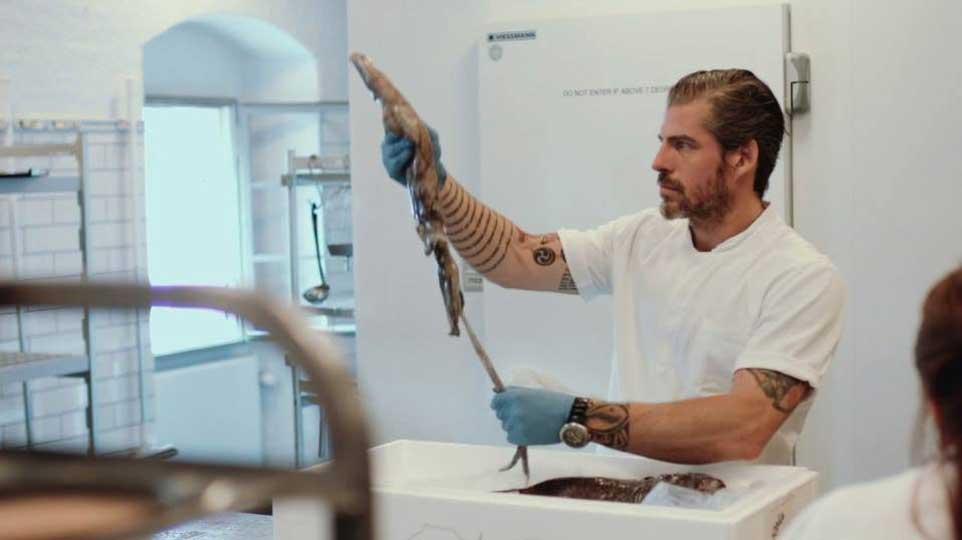 Uno dei cuochi del Noma al lavoro con un calamaro