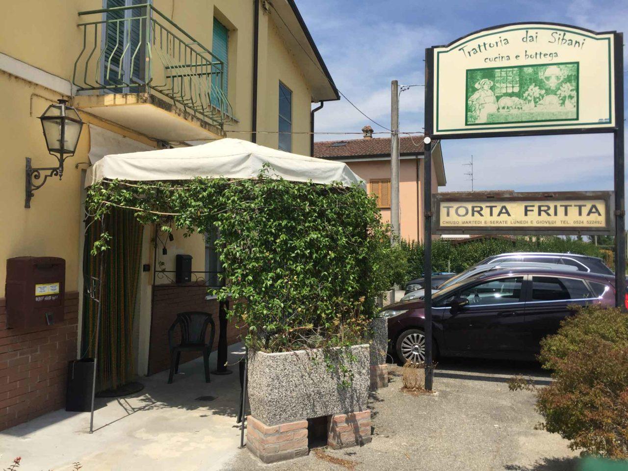Trattoria dai Sibani a Chiusa Ferranda, Fidenza: l'ingresso preceduto da un piccolo portico e l'insegna con la scritta torta fritta