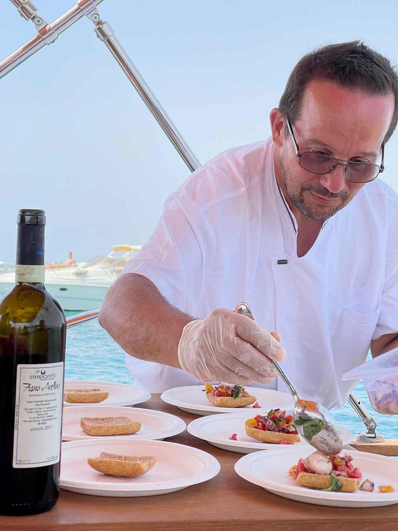 Luigi Ipaigio prepara le freselle di mare sulla barca Leucosia